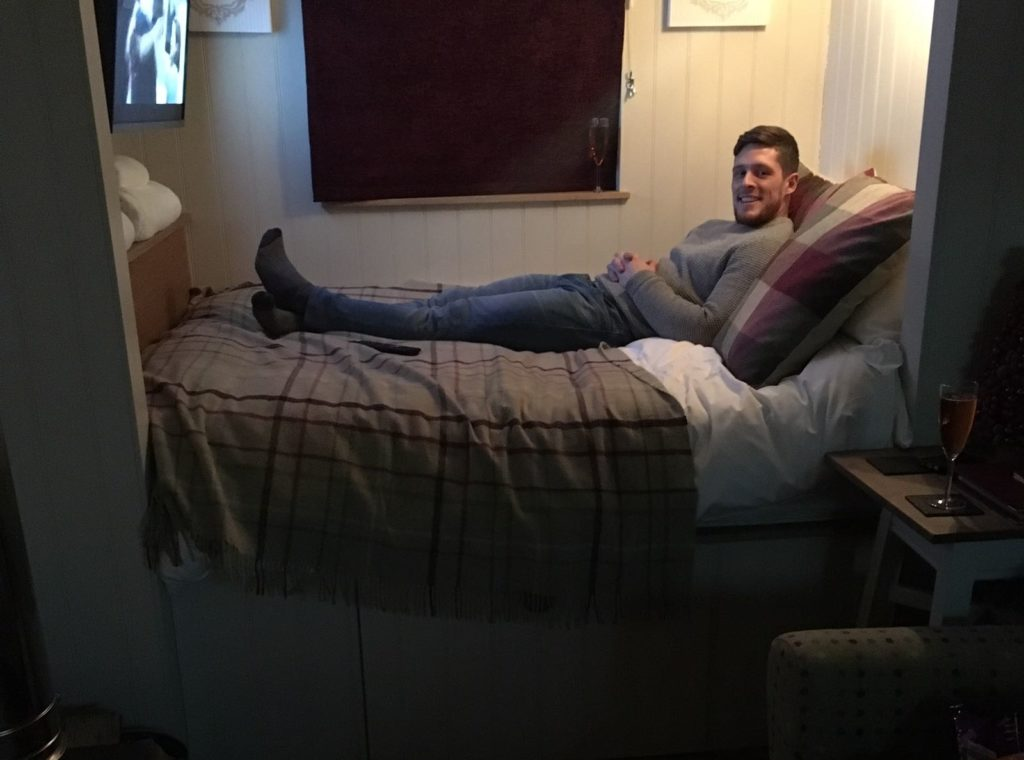 person lying on a double bed in shepherds hut