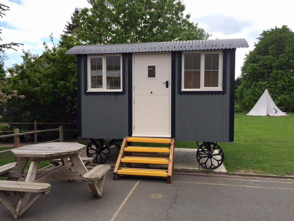 small shepherds hut with small cast iron wheels