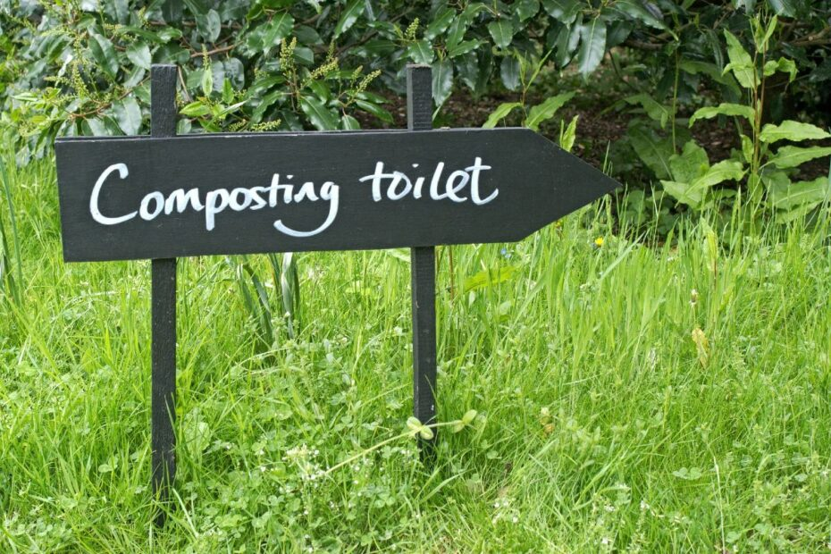 composting toilet sign on green grass