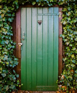 wooden toilet door surrounded by green leaves