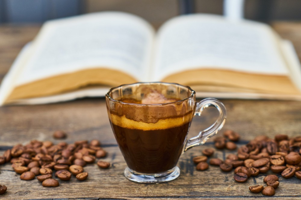short coffee in glass cup with coffee beans and an open book