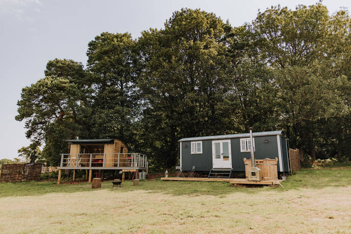 cowslip shepherds hut in a field with trees