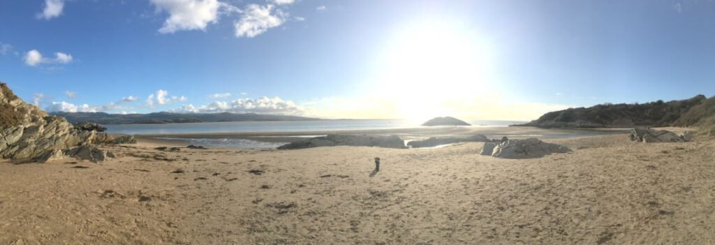deserted beach at borth-y-gest looking out to the sea with sun low in the sky