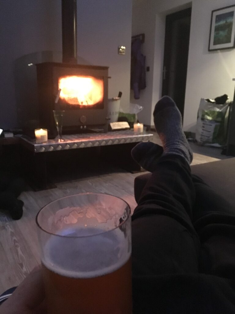 pigsty large log burner fire roaring away with beer in hand and feet up