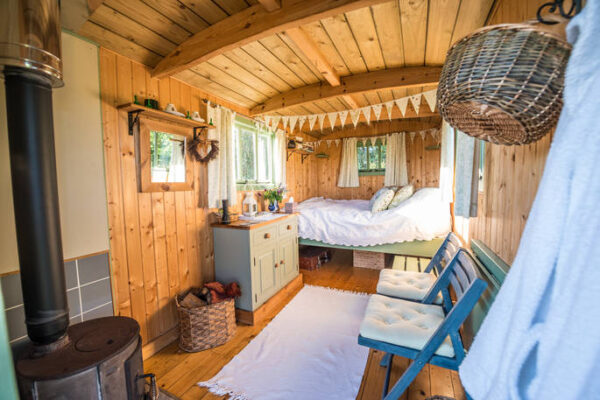 jesters shepherds hut wood clad interior with cosy bed and log burner