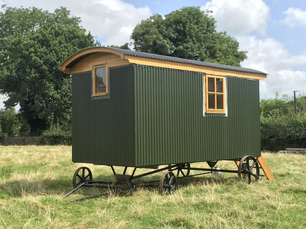 a wells shepherds hut simple hut with green corrugated iron cladding four iron wheels and a towbar
