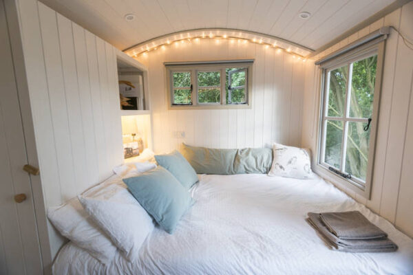 cosy white king size bed in wigeon shepherds hut essex