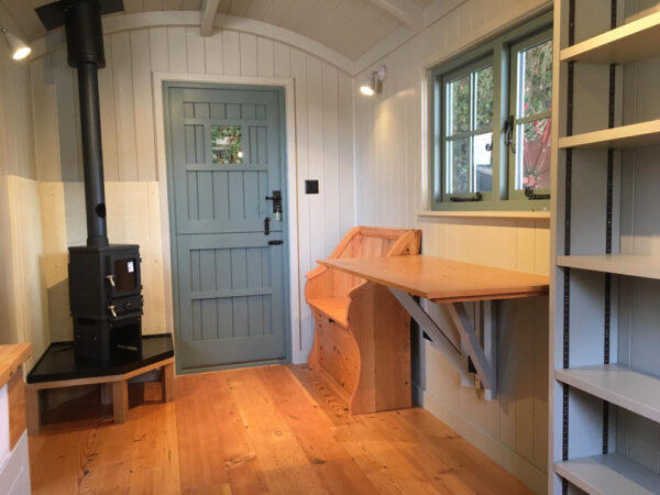 inside furnishing a self build shepherds hut with log burner and table