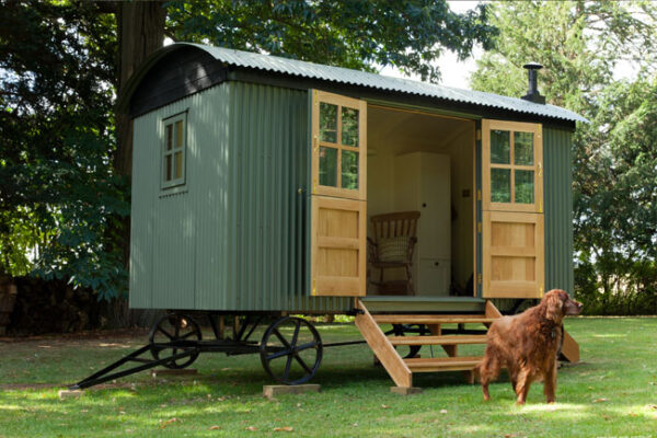 build your own shepherds hut with a shepherds hut kit from tithe barn green hut with dog outside