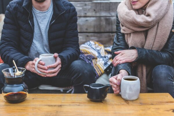 two people drinking coffee outside